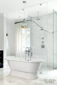 13. A nearly invisible walk-in shower is backed by a luxurious, marble-lined wall. Interior design by Betty Burgess.