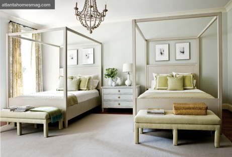 """Howard minimized the large scale of the two queen-size four-poster beds by using pale-toned painted furniture, right down to the chandelier. Myott""""s """"Departure Series I, II, III, IV"""" graces the room""""s walls."""