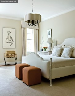 """Orange ottomans at the foot of the bed in this guest room add a little """"kick."""" Just as eye-catching is a Todd Murphy charcoal drawing on paper."""