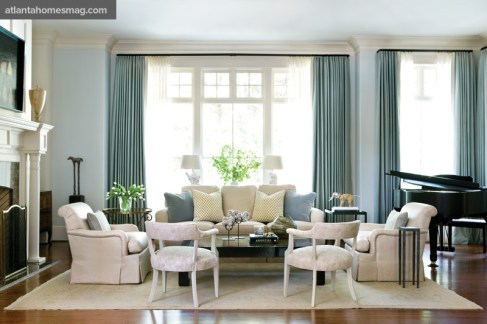 """Generous seating in the living room accommodates the homeowners"""" penchant for frequent entertaining. Pale blue linen curtains frame views to wooded vistas beyond, while sheers control sunlight throughout the day."""