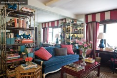 """In this studio space, boldly striped curtains frame the apartment""""s lone window. To get precisely the right stripe width, designer Lindsey Harper sewed red and white Pindler & Pindler linens together."""