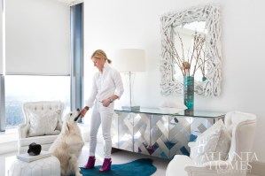 The master bedroom is clean and serene, with pops of blue in the form of an emerald hide rug, mirrored herringbone credenza and wave-stitched pillows complementing an all-white scheme. Rider, an English cream golden retriever who is also a fixture at Kleinhelter's Buckhead boutique, Pieces, is partial to the hide.
