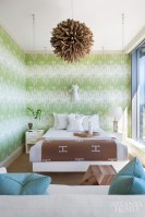 """To camouflage the building's architectural angles, the designer suspended the guest bed from the ceiling and selected a """"busier"""" wallpaper. Driftwood ball chandelier, geometric wood table, ribbed end tables, sheep, lamp and pillows from Pieces."""