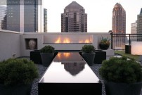 "The design of the outdoor terrace was given just as much thought as the interior space. ""The idea behind the pond is that it reflects the buildings,"" says Parrish, ""and then you have the fire that ""dances""in the water."" Reflecting pond by Atlanta Water Gardens. Plantings and containers by Planters, Inc. Hardscapes, deck and fireplace, Timoney Construction."