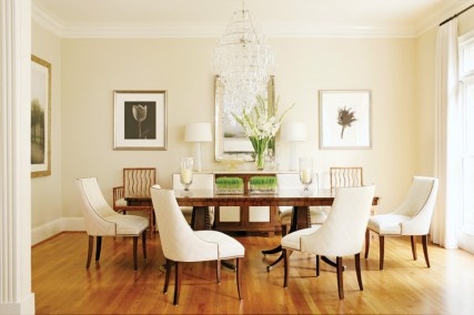 """The dining room of Tom and Karen Chapman's Buckhead townhouse is a testament to decorator Phoebe Howard's love of symmetry. She designed it around Karen's existing artwork and dining table, which the decorator describes as a """"contemporary twist on a double-pedestal table."""""""