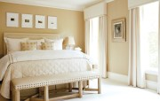 """""""The bedroom had low ceilings so, to make the space feel roomier, we used a soft mushroom color on the walls,"""" says Howard, """"Then we used ivory curtains and carpeting to soften and expand the space."""" Plush bedding in luxurious fabrics adds to the room's sumptuous feel."""