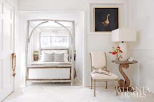 Raulet Hall created a restful sanctuary in the home's cozy master bedroom by tucking a hand-made, white-washed canopy bed inside an alcove overlooking the lake. The cowhide rug and the stained side table were purchased at Scott Antique Markets. The French side chair was found at the stalls at Denton Street Market. Linens, Restoration Hardware. Paintings by Raulet Hall. Alabaster lamp, Huff Harrington Home.