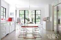 """A custom steel-framed, white oak-topped table by Stephen Balcom doubles as a cooking prep and dining space in the airy kitchen. Normark outfitted a kitchen nook with two chairs from Etsy, providing the perfect spot in which to curl up with a good book. Stockett says her favorite feature is the limestone floor from Walker Zanger; its herringbone pattern not only offers visual interest, but was """"specifically chosen to disguise dirt."""""""