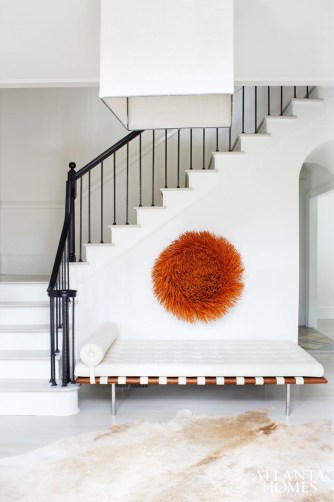 The foyer hints at the unexpected interior that lies beyond. In true Douglass fashion, the minimalist space places importance on just a few special objects: the old (the homeowners) prized Mies van der Rohe daybed), the found (a straw sculpture from the south of France) and the new (a hide rug).