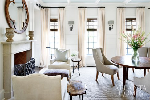 In the combination dining room-library, traditional but handsome details are tempered by curvy, feminine upholstery and draperies which puddle softly on the floor. The silvery sage hue of the coffered ceiling is one of the sole splashes of color in the neutral home. The antique breakfast table is from the homeowners' collection.