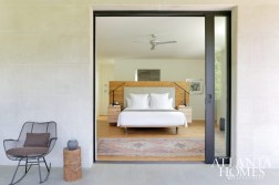 A sliding door creates a clean entrance to the terrace from the master bedroom. The custom oak headboard and pecan beside tables were fabricated from trees harvested on-site. Striped throw, The Nicholson Gallery. Pyramid sculpture, Authentique Home.