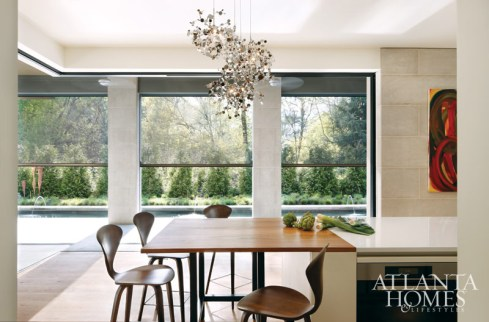 The Terzani chandelier from Illuminations hangs above the room like a silver cloud. Custom red oak table, Skylar Morgan. Cherner counter stools, Design Within Reach. Screens, Phantom Screens.