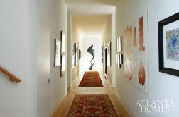 This long interior hallway on the main floor was designed to both highlight the homeowner's significant art collection and to protect tit from the sun. A contemporary sculpture by Bryan Hunt is given pride of place on the far wall and completes the gallery-like setting.