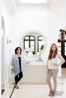 Homeowner and Beacham & Co. realtor Wendy Petersen with designer Anne Williams in the home's two-story entry. Concrete consoles by Bradley. Custom mirror by Myott Studio.