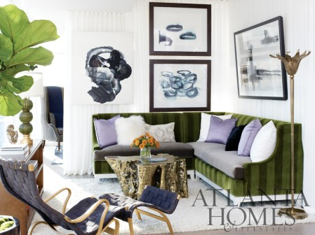 In the living room of this sun-soaked residence, the plush velvet sectional with a nail-head trim base was designed by Amy D. Morris Interiors and fabricated by artisans represented at The Mercantile. Gilded accents include a bronzed tree trunk cocktail table and a Murano glass lamp. A vintage Bruno Mathsson Pernilla chair and ottoman, with its original webbing, is nestled next to a Hanover Leather Console. Behind the linen wall, a Bjork Studio Fladdermus Wing Chair anchors the corner of the home office. All of these items are available through The Mercantile.
