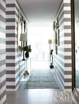 """The residence""""s bold entryway features a pair of hammered silver-leaf skinny consoles. All of these items are available through The Mercantile."""