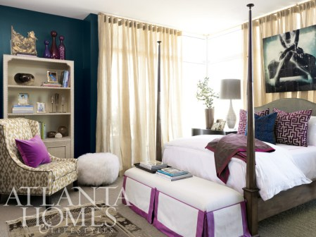 At the foot of the four-poster bed sits a vibrantly accented custom bench up-holstered in Bergamo fabrics. The colorful hue is repeated on a throw and decorative pillow. The Fenwick Chair is covered in a gold fabric and has a vintage nail-head finishing. The bedside console features a glass-and-acrylic lamp, while the raffia-covered cabinet displays items like an antique architectural plaque and colorful hand-blown glass jars by Elizabeth Lyons. All of these items are available through The Mercantile. Fabric for the window sheers was provided by Jim Thompson.