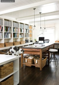 """Book- and basket-lined shelves create order in designer Barbara Westbrook""""s relaxed office space, which mixes modern and traditional through contemporary pendant lighting and an antique French baker""""s table."""