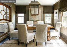 """In the conference room, slipcovered Parson chairs and a flatweave rug from Sullivan Fine Rugs create an interesting contrast to the space""""s earthier tones, from the walls, painted in Satchel by Benjamin Moore, to an overscale patinaed lantern and French oak table."""