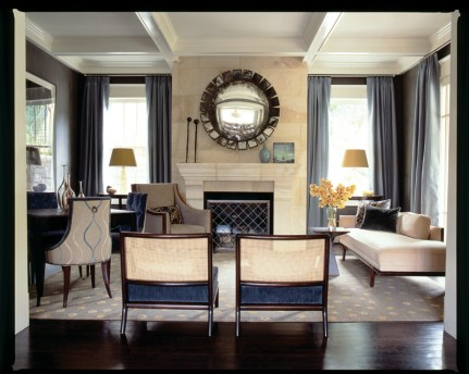 """""""I wanted it to feel like a lounge, dark and cozy,"""" says designer Brian Watford of the living room, where dark brown plaster walls add depth to the space. There""""s plenty of comfortable seating, too, including a vintage daybed and a pair of cane-back, vintage- inspired slipper chairs opposite of the fireplace, intentionally low so as not to block the view as you enter the room."""