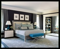 """""""The master bedroom is enormous, as large as the kitchen, breakfast room and family room combined,"""" Watford says, """"so the challenge was to make such a large space feel cozy without being cluttered."""" By upholstering the walls in charcoal gray wool, the designer not only wrapped the room in warmth but also found a way to control echo, given the generous dimensions. In turn, the walls became the foundation for a simple gray-and-white scheme with pops of deep turquoise throughout the space."""