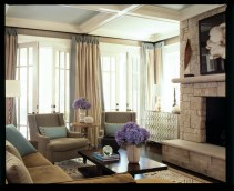 """A stacked-stone fireplace establishes the family room as a causal space with a slightly rustic feel. """"The walls needed more than just paint, so I covered them in a chevron-patterned grasscloth, adding another layer of texture,"""" Watford explains. It""""s softened, he adds, by floor-to-ceiling linen draperies banded in a contrasting linen, picking up the turquoise blue accent color in the rug and pillows."""