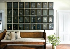 """Expertly arranged art groupings are found in both of Stanton""""s homes. In the hallway of the country house, a moody assortment of pressed botanicals, set on black paper and framed by Soho Myriad, pay tribute to the natural world just outside. All furnishings, artwork and accessories, Stanton Home Furnishings."""