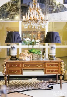 Chovan and Loftin create an enticing vignette with this antique brown-and-white zebra hide, Louis XVI-style desk with rare mermaid mounts and a pair of mid-century modern lamps.