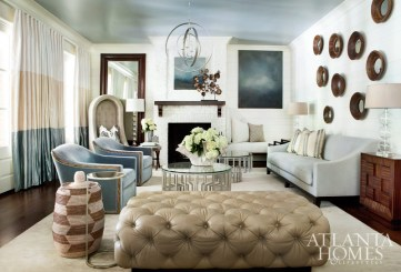 In the family room, which overlooks the pool and pavilion, a blue-gray toned ceiling and soft, solid upholstered pieces create a calming retreat. Jessica chandelier and artwork from Bradley.