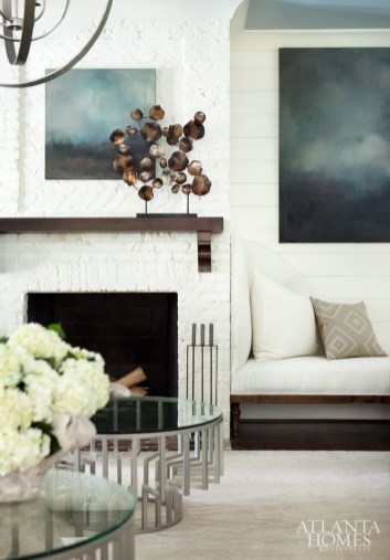 In the family room, Boyd fashioned subtle sophistication with an artful arrangement of distressed teak mirrors, a custom, rounded-back chair and white bench by SmithBoyd Interiors.