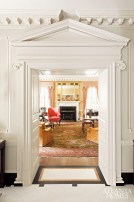 """Askins pulled out all the stops to craft this rich Georgian-style interior marked by a pedimented doorway that frames the drawing room. Every element embraces historic precedent and appropriateness. """"Nothing was left to chance,"""" says Askins. """"All floors, ceilings and walls were carefully detailed accordingly."""" The architect's team also designed the striking millwork, living room mantelpiece and even the custom gilt mirror that crowns it."""