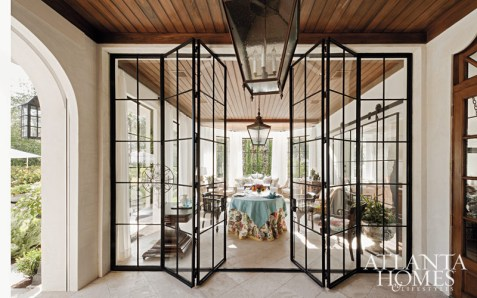 For a pair of former Chicago dwellers' Sea Island residence, Askins's firm employed folding-steel French doors to separate the glass conservatory from the adjacent loggia, both of which overlook a swimming pool and tree-lined vista beyond.