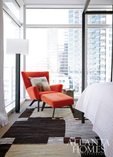 A tangerine Boden Chair and Ottoman sits next to a Duo Floor Lamp.