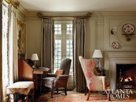 A collection of antiques in the formal living room is enhanced by rich design elements, including silk draperies and the vibrant early 20th-century Oushak carpet. A Philadelphia slant top desk, English easy chair and Royal Crown Derby porcelain become prominent when framed against the muted taupe of the walls and trim.