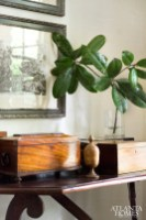 A set of tree engravings from Foxglove Antiques hangs above a wood console, which showcases personal treasures like an antique carved box.