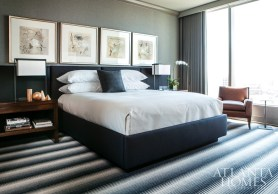 """The master bedroom is completely wrapped in gray flannel, from the upholstered walls to the draperies. """"When the draperies are closed-they're motorized-the room is totally blacked out, which is nice because the owner travels internationally, and he can sleep no matter what time zone he's in,"""" Brown says. """"I love the acoustical quality of the upholstered walls; it's so quiet."""" Bedside tables from Baker and lamps from Holly Hunt flank a custom bed. French drawings from T. Botero Galleries hang above it. The carpet is Missoni, available through Stark."""