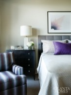 Like the rest of this residence, a guest room is elegantly understated, with the gray flannel channel-quilted bed accented with pops of purple. A Baker lamp sits atop a chest by Hickory Chair.