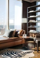 """Inspired by a gray flannel suit """"with a great brown leather belt and brown shoes,"""" Brown opted for a custom leather chaise and a pull-up chair totally upholstered in gray flannel, matching the draperies. The glass-and-steel shelves are from Smith Grubbs & Associates."""