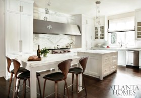 The homeowners wanted an all-white kitchen, and Westbrook delivered a space that's as light and bright as it is visually interesting. Because the room opens up to the main floor's most public spaces, she created a focal point in the form of a long slab of bookmatched Calacatta Conti marble, topped by a stainless steel hood. A kitchen table and island, both topped with 2 1/2-inch countertops and identical in size, break up the visual plane. The barstools and pendant lights are from Switch Modern. The custom cabinetry is by Kingdom Woodworks.