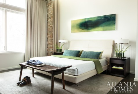 """""""The bench at the foot of the bed is a nice way to relieve the modern pieces,"""" says Kelly of the couple's accent seating, which is an unexpected juxtaposition to the leather headboard and custom nightstands in the master bedroom."""