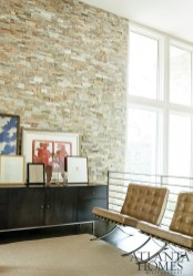 Overlooking the ground floor is the light-filled office, with a curated display of the couple's artwork on a credenza flanked by a set of leather Barcelona chairs. The slatted stairwell delivers more architectural drama.