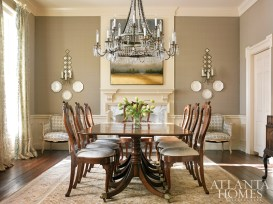 A David Iatesta scalloped tole chandelier from Ainsworth-Noah commands the dining room. It hangs above an inherited dining table and chairs and a traditional rug from Sullivan Fine Rugs. Creamware plates from Interiors Market are displayed on walls upholstered in a fabric by Boussac, available through Travis & Co. The 19th-century bergere chairs were found at Foxglove Antiques & Galleries, then updated with a contemporary fabric from Galbraith & Paul. The diamond-patterned sconces are from Parc Monceau. Curtain fabric is Pierre Frey, available through Travis & Company.