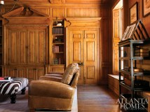 """The paneling in the stately library was designed by Dixon, constructed from hemlock and expertly finished by local artisan Hal Jones. """"This room is the gem of the house,"""" says Dixon. The book stand is from MacRae."""