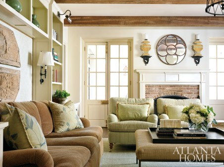 In the family room, architectural remnants hang above the sofa, while a quatrefoil mirror from MacRae provides a focal point above the fireplace. Edward Ferrell + Lewis Mittman club chairs are from Ainsworth-Noah.