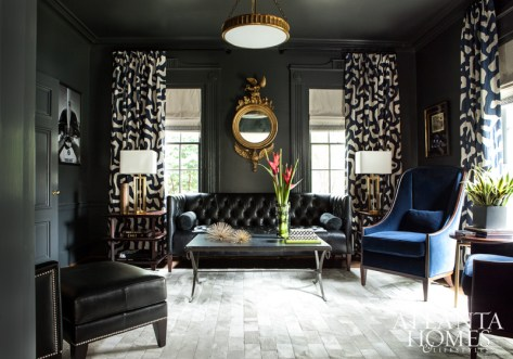 """Clary discovered the library curtain fabric, """"L'Africain"""" by Jed Johnson Home, which both designers would subsequently use in other projects. Not only does the tribal print add warmth, lushness and edge to the room, but it's also appropriate, considering the homeowners' love of Africa. A pale Stark Carpet hide rug offsets the deep graphite color of the room's walls and ceiling."""