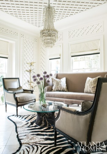 """Gracing one end of the house is the """"ladies drinking parlor,"""" whose trellage was added by architectural designer Duane Stone during a late-1990s renovation. A zebra skin rug accentuates the first floor's predominantly black-and-white color scheme, while a Warren Platner chrome-and-glass cocktail table marries well with the antique crystal chandelier. An Edward Ferrell + Lewis Mittman sofa and two Louis XVI-style chairs by Wesley Hall provide comfortable seating for meetings and socializing."""