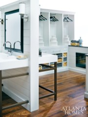 """What makes this bath truly remarkable is that there are so few items straight from stock."" For example, the sink units with metal bases were made exclusively for this space. Other custom elements include antique wide-plank walnut flooring from Atlanta Specialty Woods and cabinetry by Bell Kitchen & Bath Studios. Double-sided sink vanities create a partition between the bath's wet and dry zones. The latter area features a ventless fireplace from Builder Specialities with an adjacent beverage center outfitted with Sub-Zero and Wolf appliances."