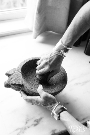Nygren grinds spices with a mortar and pestle.