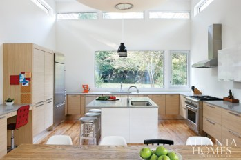"""The open-format, eat-in kitchen contains sleek wood and glossy SCIC laminate cabinetry. The clerestory windows were a Frank Lloyd Wright-inspired touch. """"From the kitchen, you can see straight up to the sky,"""" Carpenter intimates."""