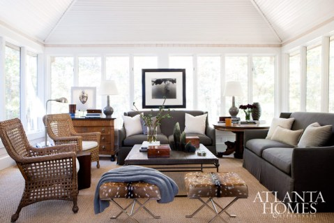 Floor-to-ceiling windows in the sunroom of designer Robert Brown's Lake Hartwell home offer scenic views. Many of the furnishings have been collected over the years, including a pair of sofas he purchased for a designer showhouse, and the circular end table that once served as the Brown family dining table. The mid-century chrome and deer hide stools are from Brown's Buckhead boutique, Townhouse, as is the Auguste Garufi portrait, which is displayed on an antique chest.